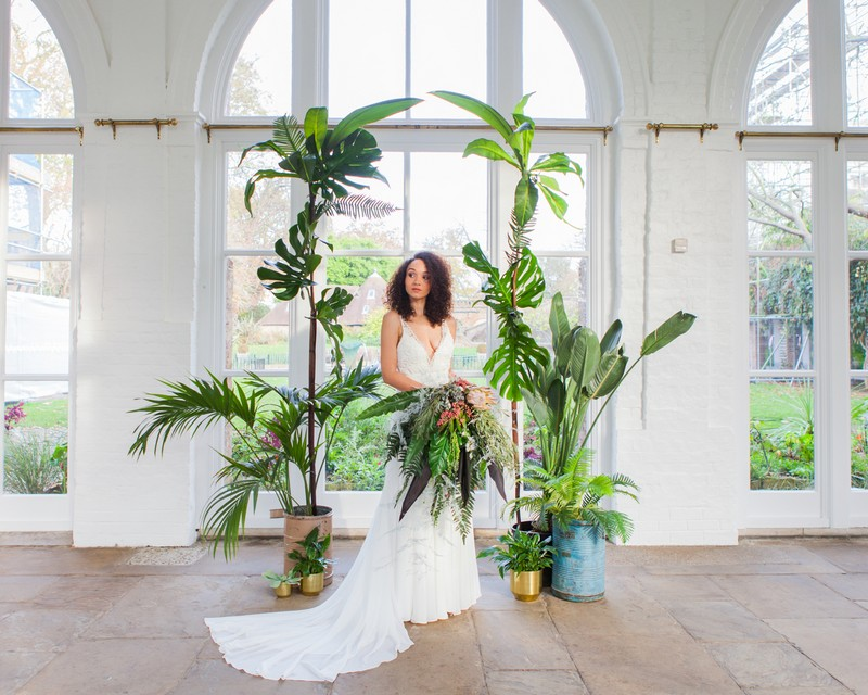 Bride standing in front of wedding arch styled with tropical foliage and leaves