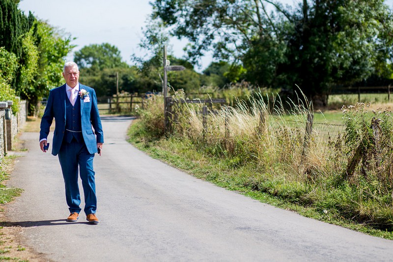Groom in blue suit walking to wedding
