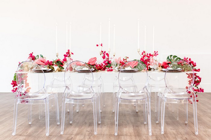 Ghost chairs in front of wedding table styled with bougainvillea