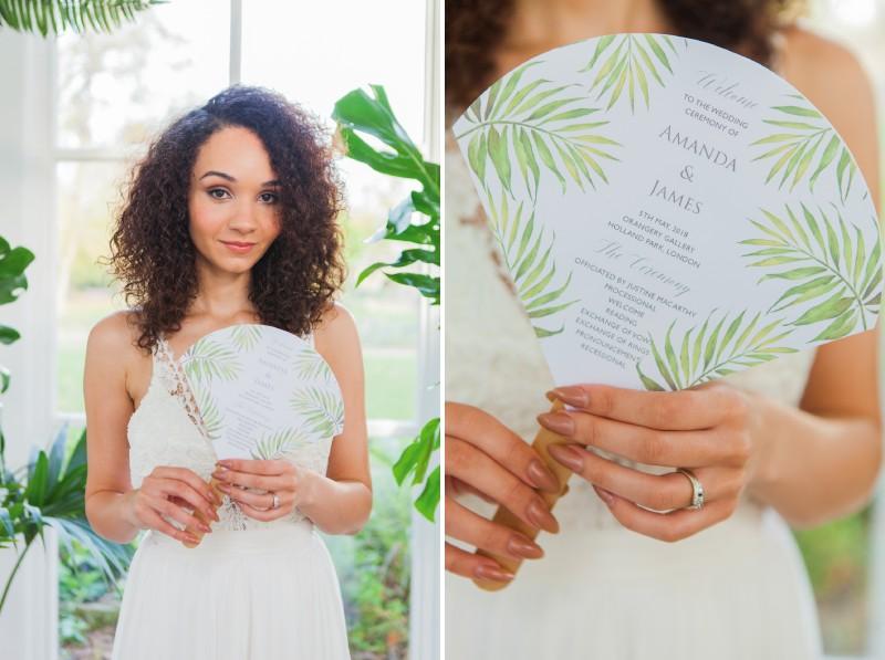 Bride holding wedding order of service fan with tropical leaf design
