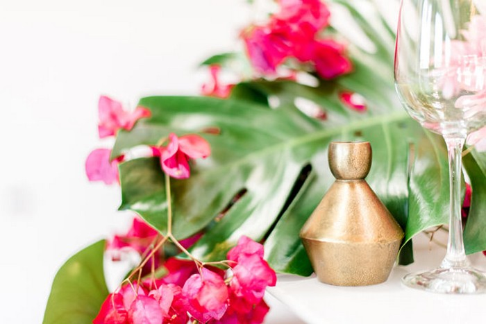 Bougainvillea and tropical palm leaves on wedding table with gold decoration