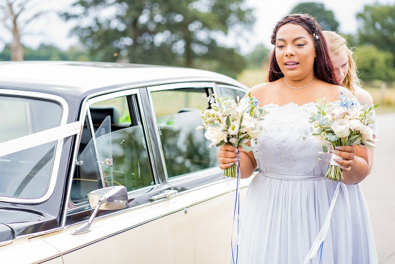 Bridesmaid carrying flowers from wedding car