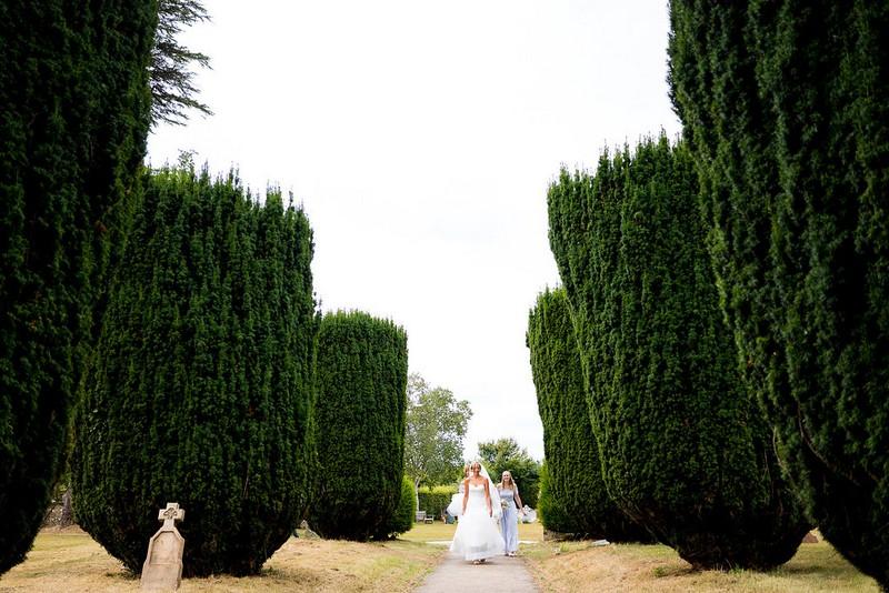Bride walking down path to church