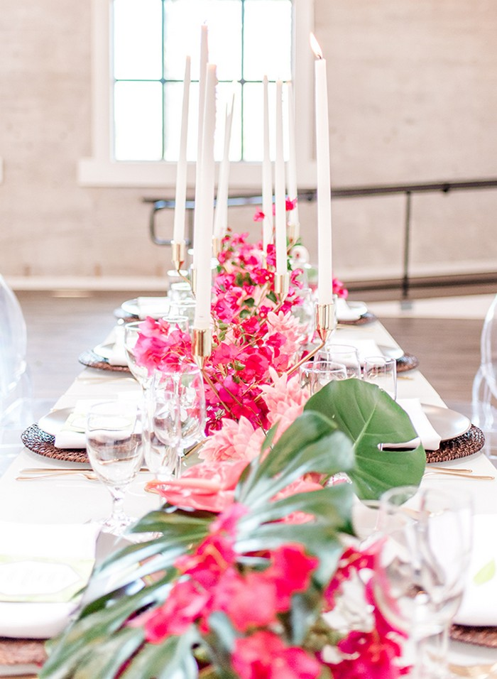 Bright pink bougainvillea and tall candles down centre of wedding table