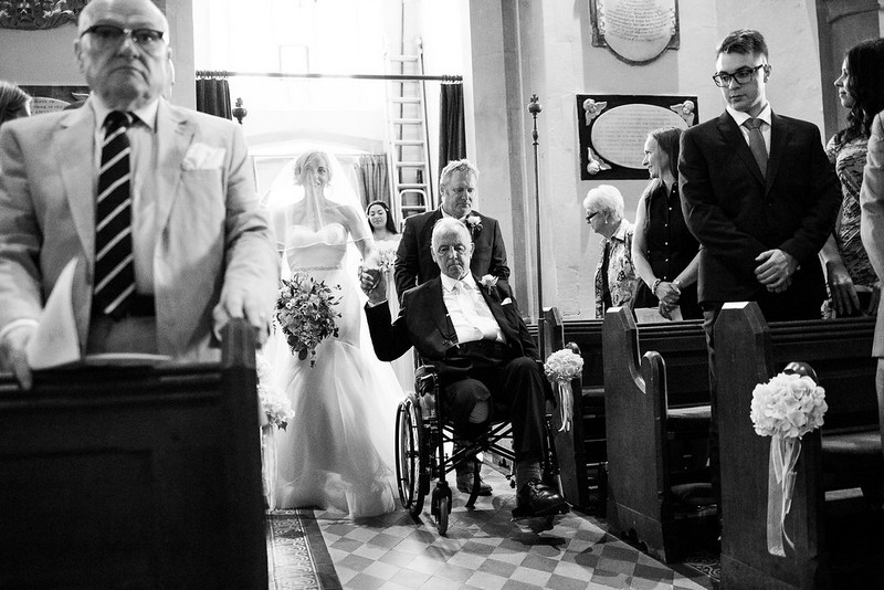 Father in wheelchair walking bride down the aisle