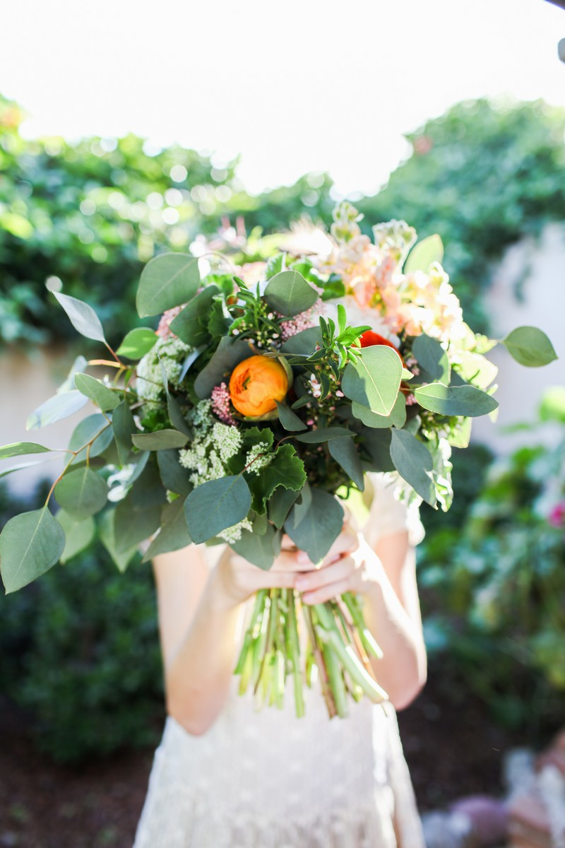 Flower girl holding bouquet in front of her face