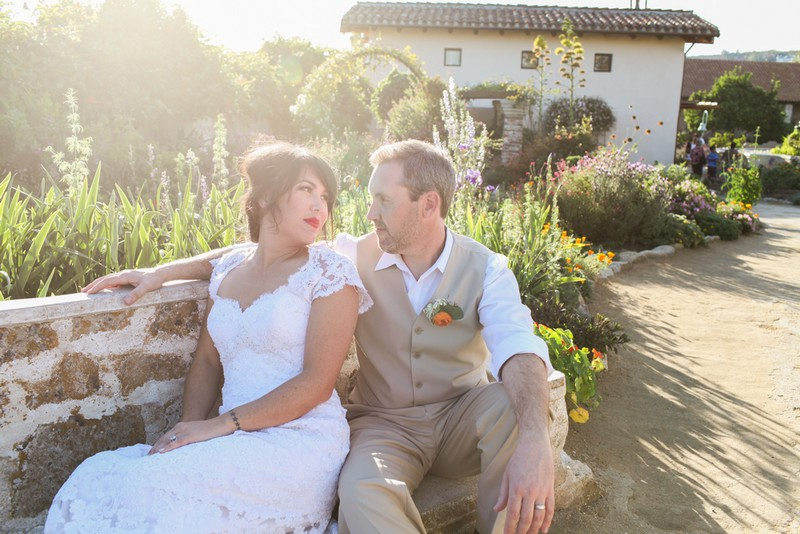 Bride and groom sitting on bench in hazy sunshine