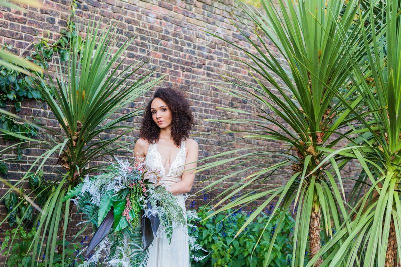 Bride holding tropical bouquet next to long grass plants
