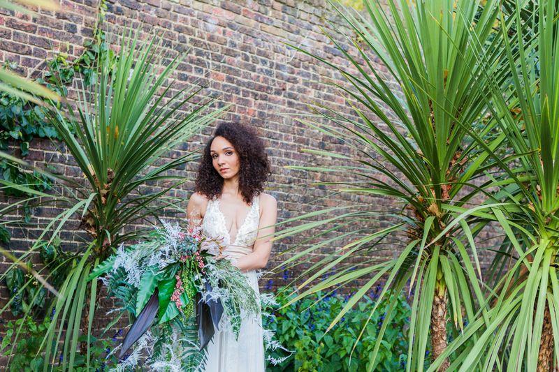 Bride holding tropical bouquet next to long grass plants