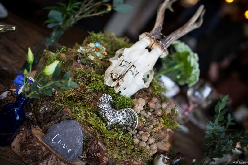 Skull and cockrell ornament on moss and log slices for wedding table centrepiece