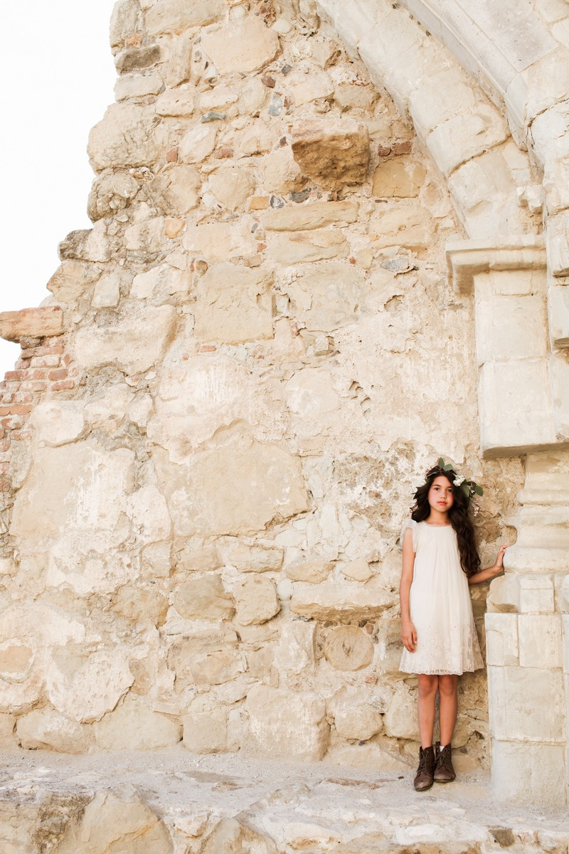 Flower girl standing by rustic wall