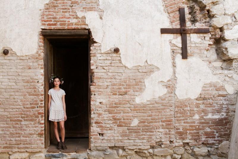Flower girl standing in doorway of old building
