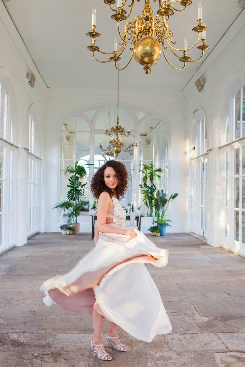 Bride twirling in dress in Holland Park Orangery