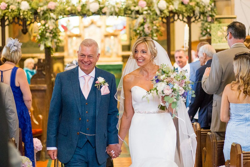 Bride and groom smiling as they leave church after wedding ceremony