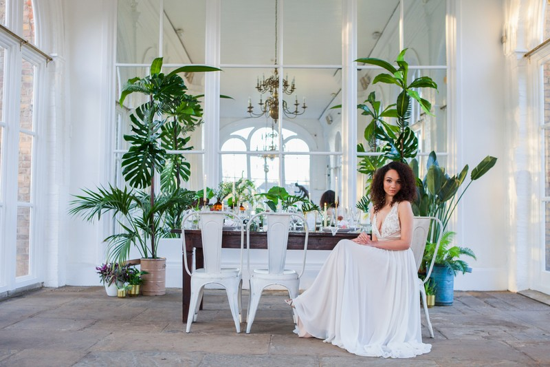 Bride sitting at wedding table in Holland Park Orangery