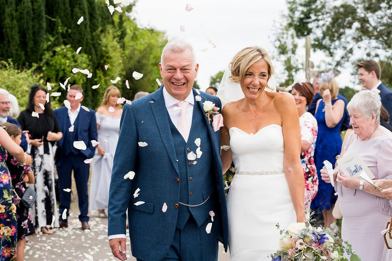Bride and groom being showered with confetti after wedding ceremony