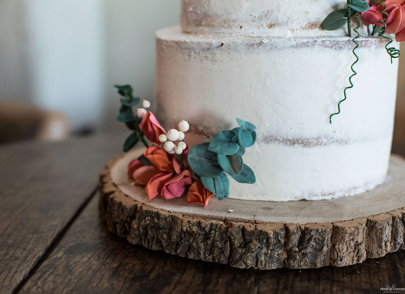 Orange flowers on log slice at bottom of wedding cake