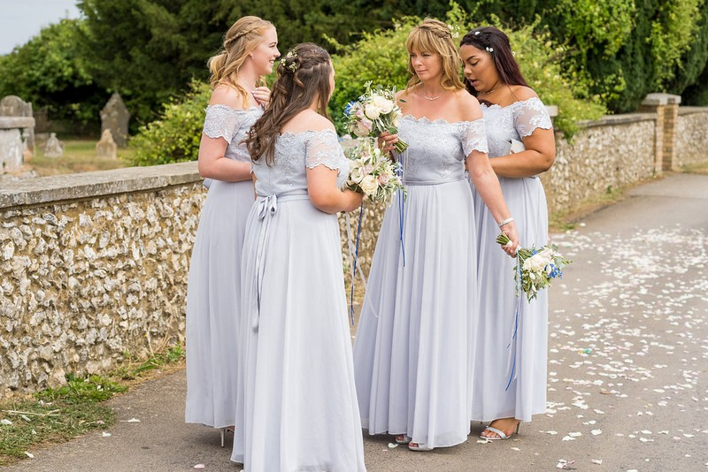 Bridesmaids outside church wearing blue/grey dresses