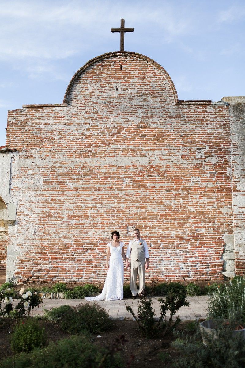 Bride and groom standing in front of wall