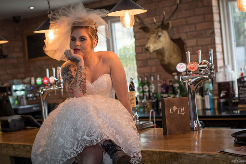Bride sitting on bar at Lyth Valley Country Inn