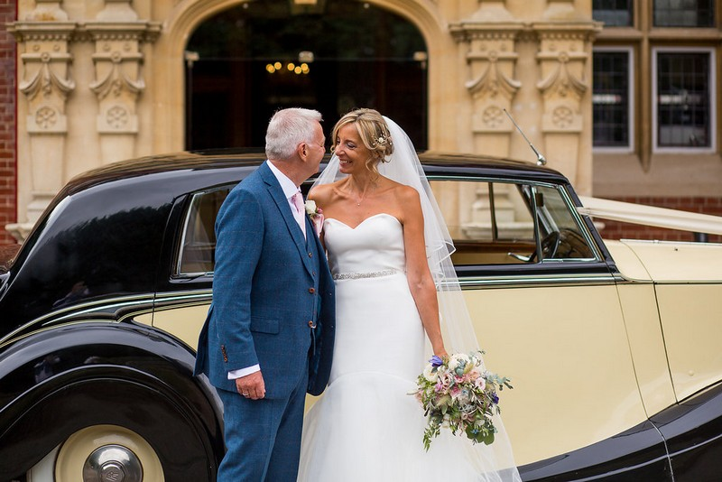 Bride and groom in front of vintage wedding car