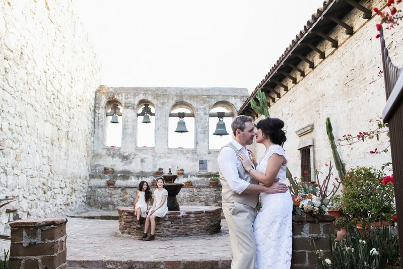 Bride, groom and flower girls in courtyard with fountain and bells