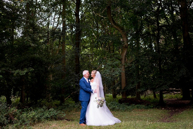 Bride and groom in woodland at Pendley Manor