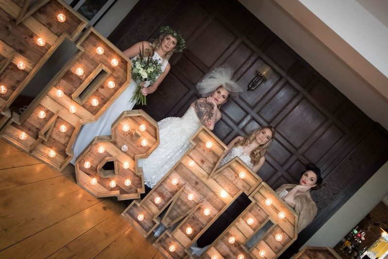 Four brides behind large light up wooden letters