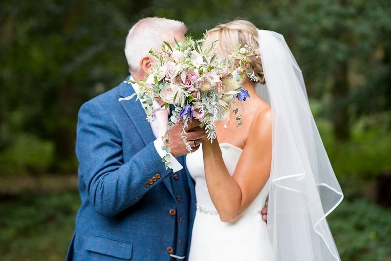 Bride and groom hiding faces behind bride's bouquet