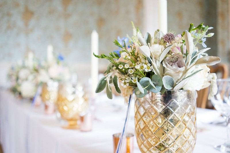 Gold glass vase of garden wedding flowers