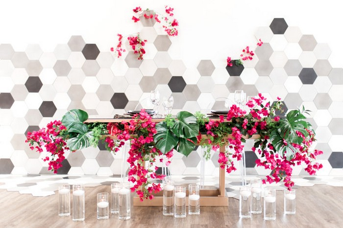 Wedding table styled with bougainvillea and palm leaves in front of hexagonal backdrop