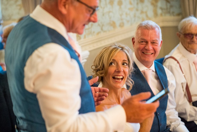 Bride smiling as man gives wedding speech