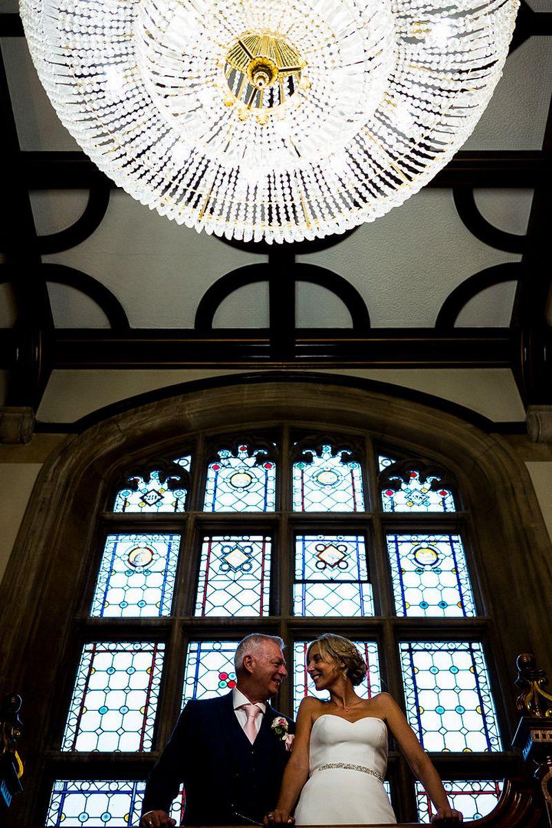 Bride and groom under chandelier at Pendley Manor