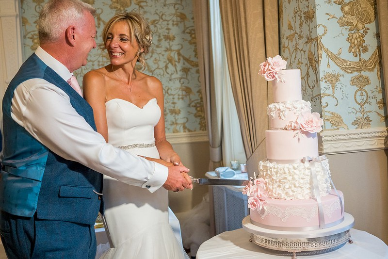 Bride and groom cutting pink wedding cake