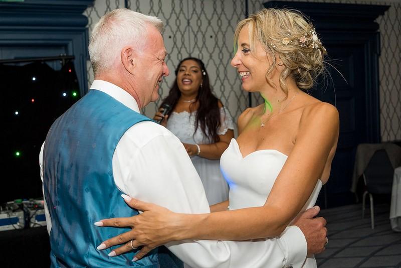 Bride and groom dancing as bride's daughter sings