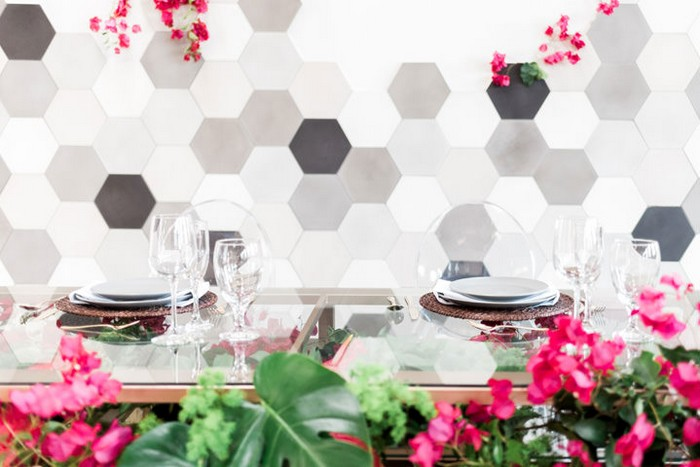 Glass wedding table in front of hexagonal backdrop