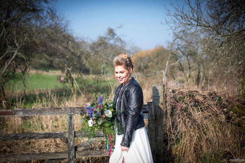 Bride in leather jacket standing by gate in countryside