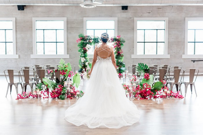 Bride standing in front of ceremony backdrop and seating tropically styled with bougainvillea