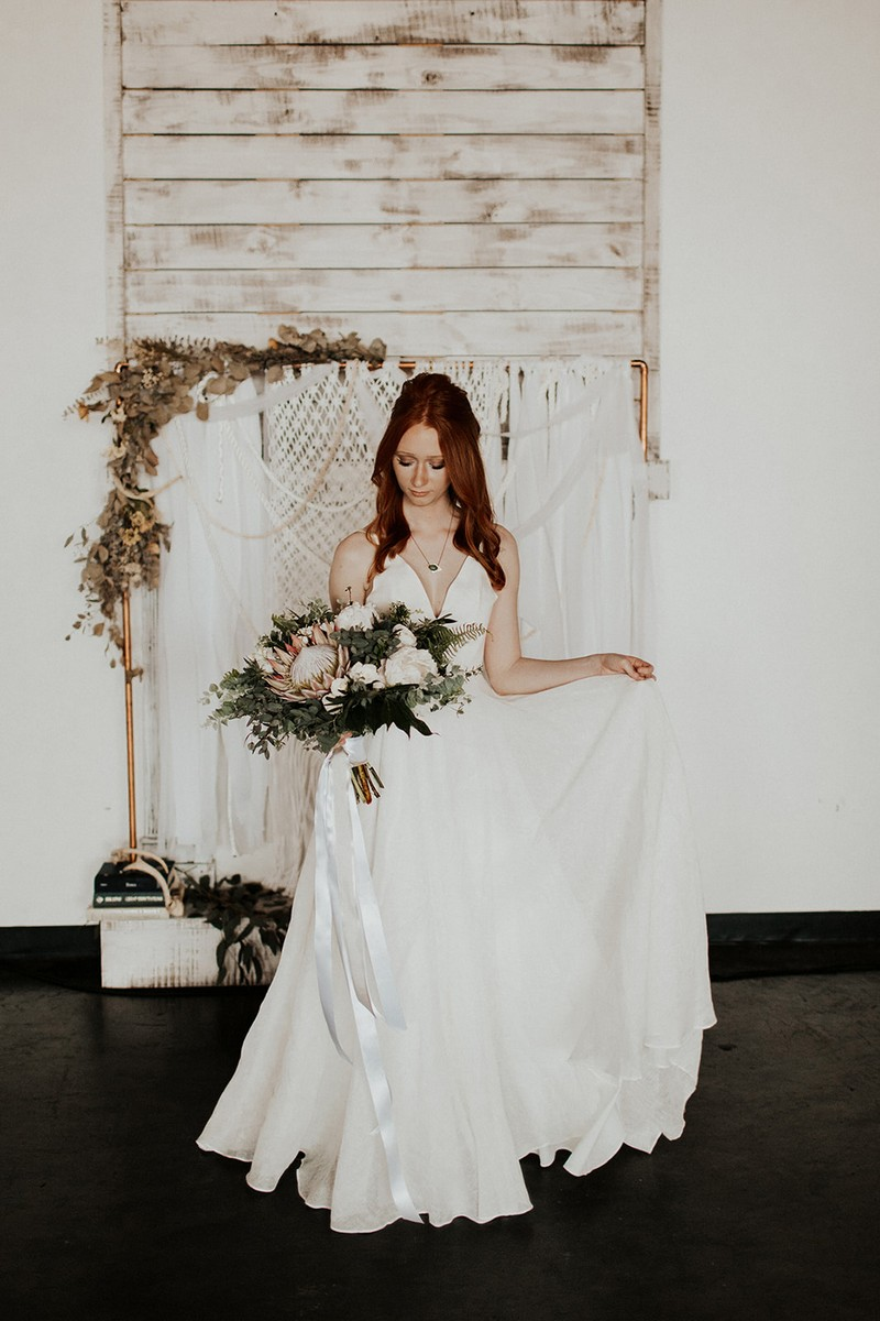 Bride holding bouquet in front of macramé backdrop