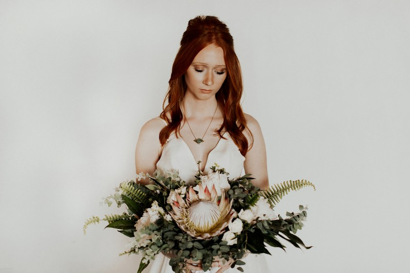 Bride holding bouquet with large flower