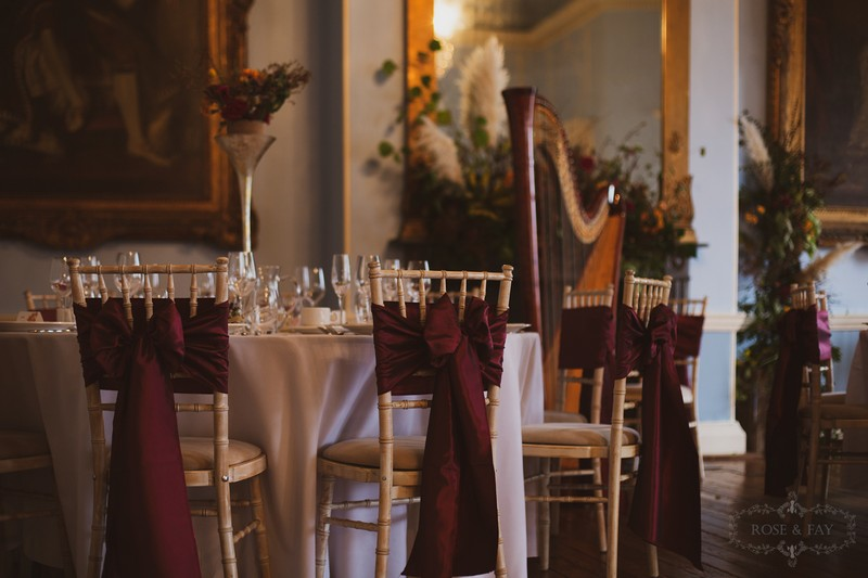 Burgundy sashes on wedding chairs
