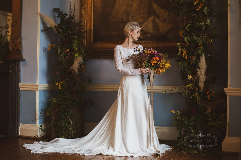 Bride in long sleeved dress holding autumnal bouquet