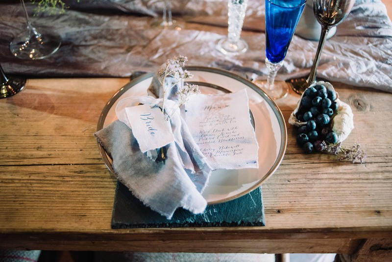 Wedding place setting with grey napkin and silver rimmed plate