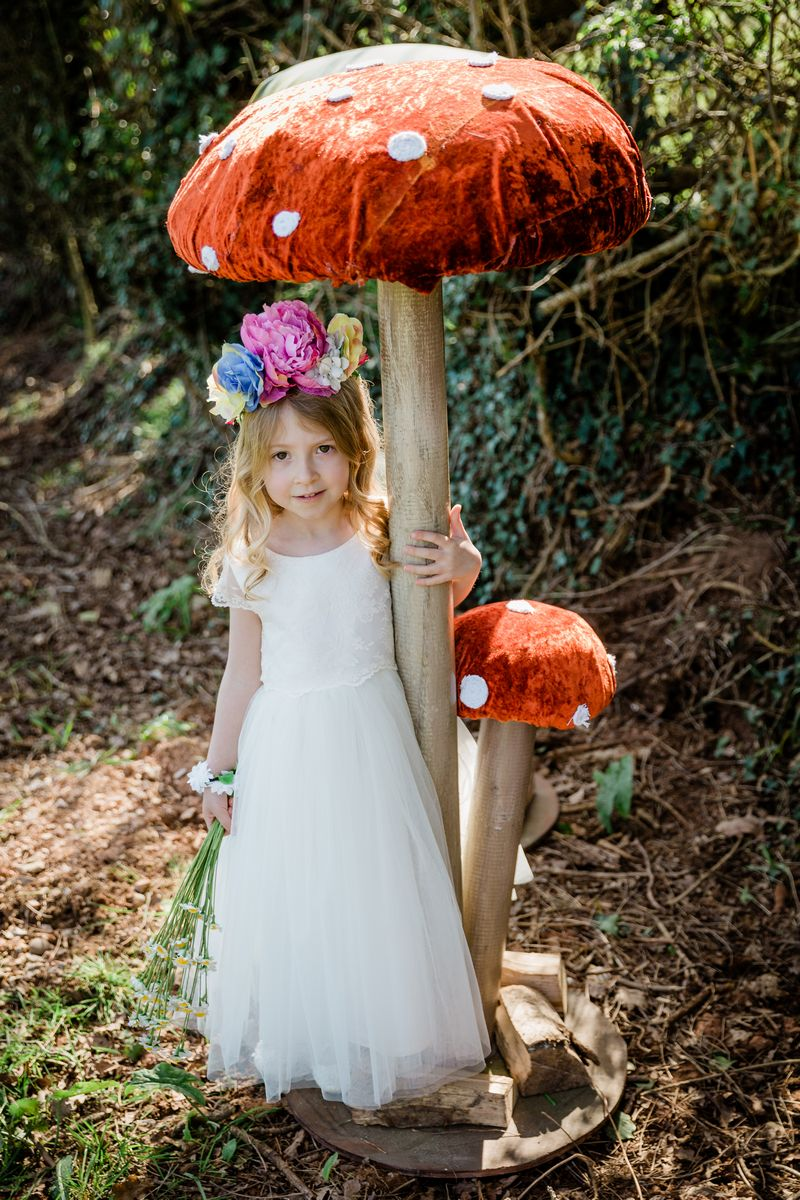 Flower girl standing under Giant Toadstool from The Prop Factory