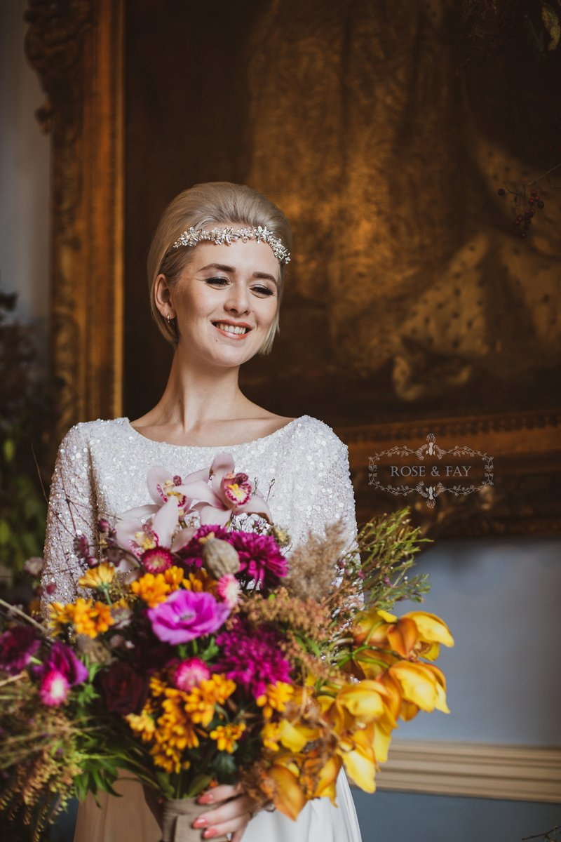 Bride holding autumnal bouquet with bright flowers