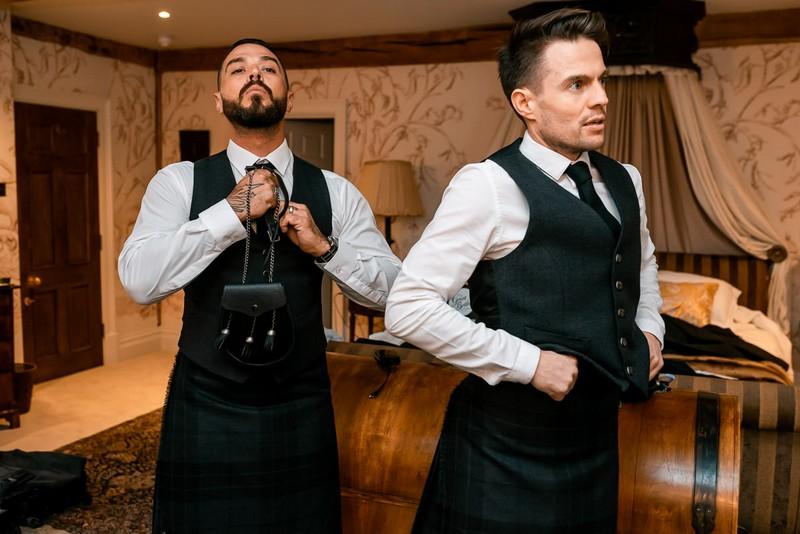 Groomsmen getting dressed into Scottish wedding attire