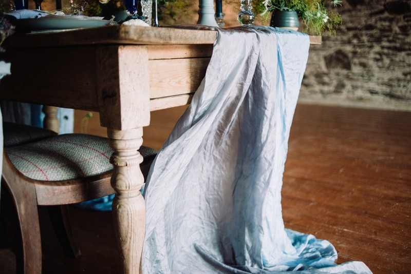 Light grey/blue linen hanging off end of wedding table