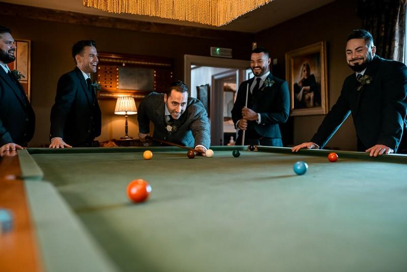 Groomsmen playing snooker before wedding