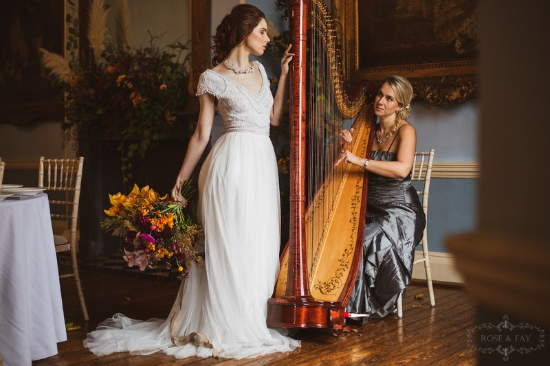 Bride standing next to wedding harpist