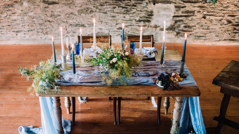Wedding table styled with rustic blue and grey details and wild flowers and foliage